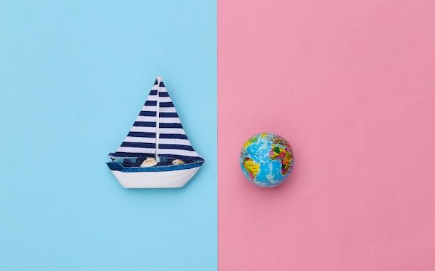 Veleiro e globo sobre um fundo rosa azul. conceito de viagens do minimalismo. vista do topo. postura plana