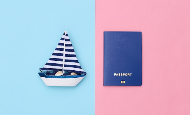 Veleiro e passaporte em um fundo rosa azul. conceito de viagens do minimalismo. vista do topo. postura plana