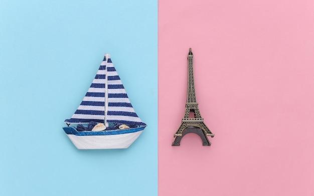 Veleiro e torre eiffel em um fundo rosa azul. conceito de viagens do minimalismo. vista do topo. postura plana