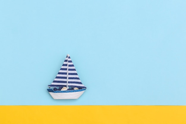 Veleiro em um fundo azul-amarelo. conceito de minimalismo de viagens. vista do topo. postura plana