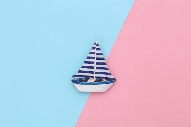 Veleiro em um fundo rosa azul. conceito de minimalismo de viagens. vista do topo. postura plana