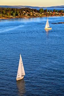 Veleiro navegando em direção ao pôr do sol em uma noite tranquila