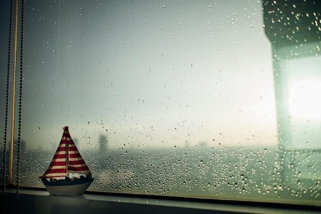 Veleiro pequeno na borda de janelas chuvosas.