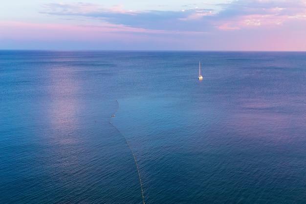 Veleiro sozinho no horizonte contra o mar azul calmo à luz do sol da noite do pôr do sol rosa