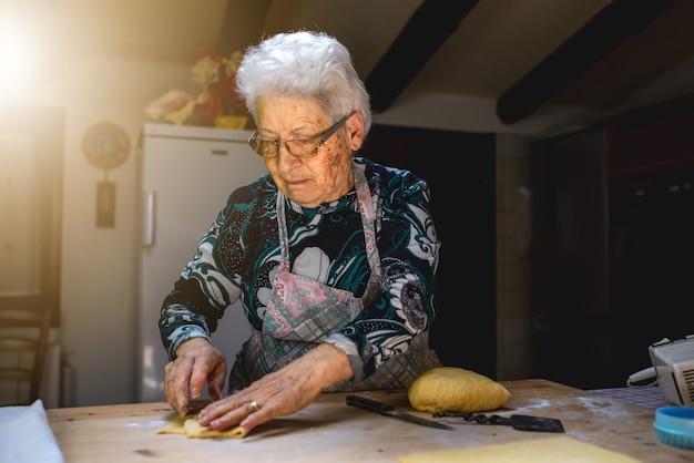 Velha amassando a massa em uma tábua de madeira na cozinha dela. preparando comida tradicional e massas