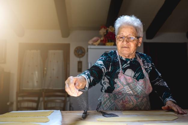 Velha amassando a massa em uma tábua de madeira na cozinha dela.