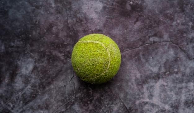 Velha bola de tênis verde gasto e empoeirada
