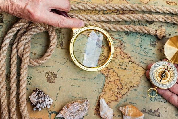 Velha bússola retrô vintage, lupa no mapa do mundo antigo