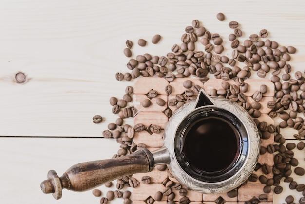 Velha cafeteira de cobre e grãos de café, vista superior