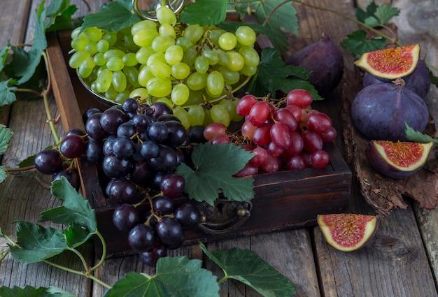 Velha caixa de uvas escuras, vermelhas e claras, figos e em torno de folhas de uva