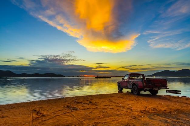 Velha caminhonete estacionada à beira-mar com pôr do sol no reservatório de bang phra, sriracha chon buri, tailândia