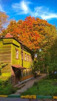 Velha casa de madeira entre folhagens de outono
