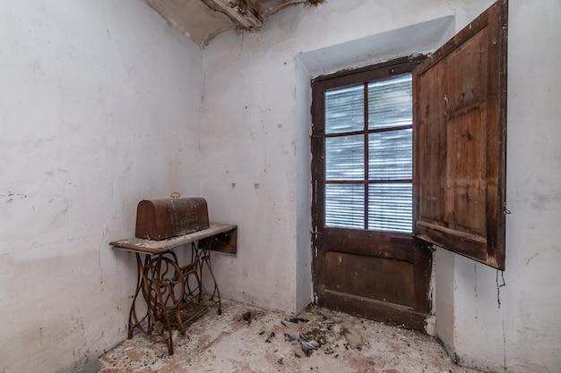 Velha esquecida máquina de costura em uma casa abandonada