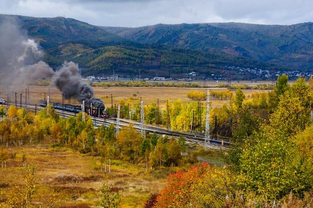 Velha locomotiva a vapor na ferrovia circum-baikal com fumaça no outono