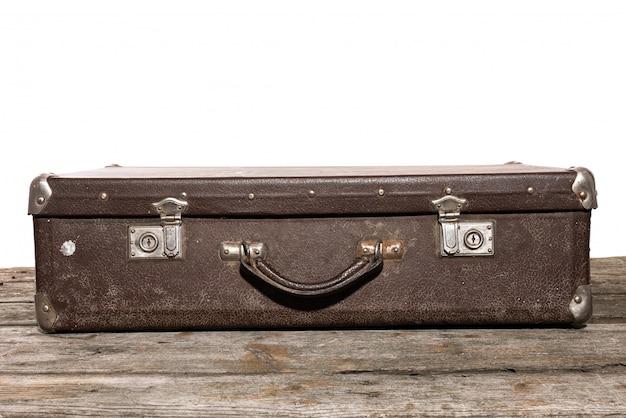 Velha mala marrom para viagens mentiras sobre a mesa de madeira