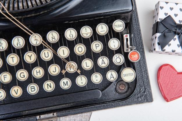 Velha máquina de escrever com uma jóia para o dia dos namorados