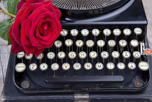 Velha máquina de escrever com uma rosa vermelha