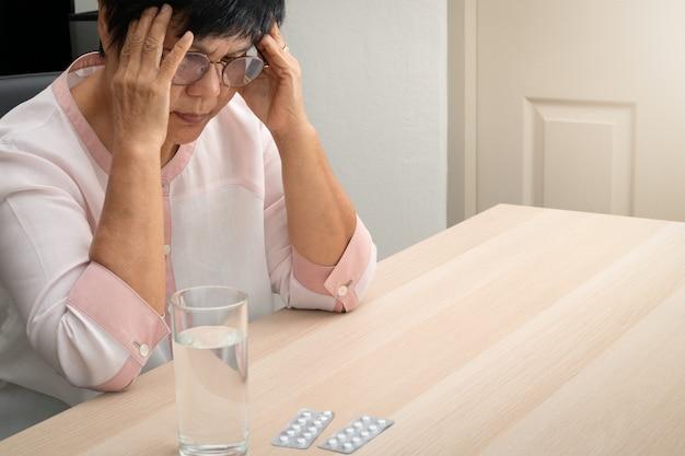 Velha mulher que sofre de dor de cabeça, estresse, enxaqueca, conceito de problema de saúde