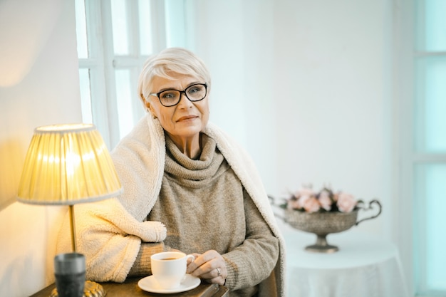 Velha mulher relaxando em casa e bebendo chá