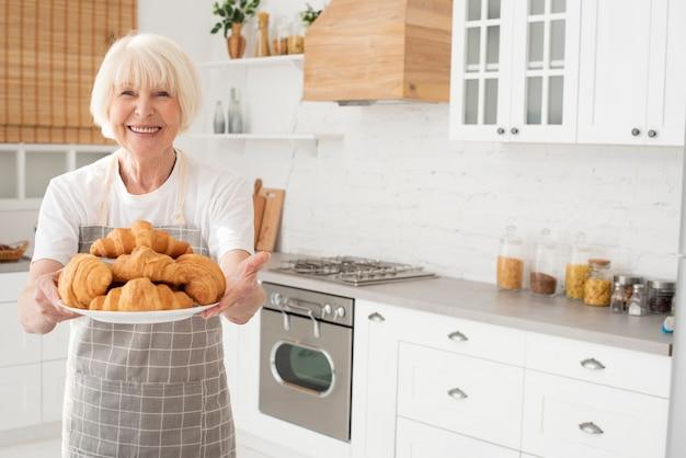 Velha mulher segurando um prato com croissants