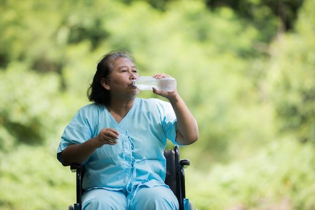 Velha mulher sente-se na cadeira de rodas com garrafa de água depois de tomar um remédio