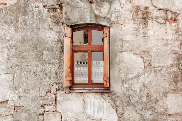 Velha parede de tijolos com janela de madeira