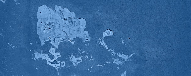 Velha parede monocromática rachada. fundo de textura pintada na cor calma na moda. bandeira. cor azul e calma na moda.
