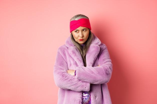 Velha senhora asiática mal-humorada e funky olhando por baixo da testa, fazendo beicinho e olhando para a esquerda com uma cara zangada e decepcionada, em pé com um elegante casaco de pele falsa roxo contra um fundo rosa