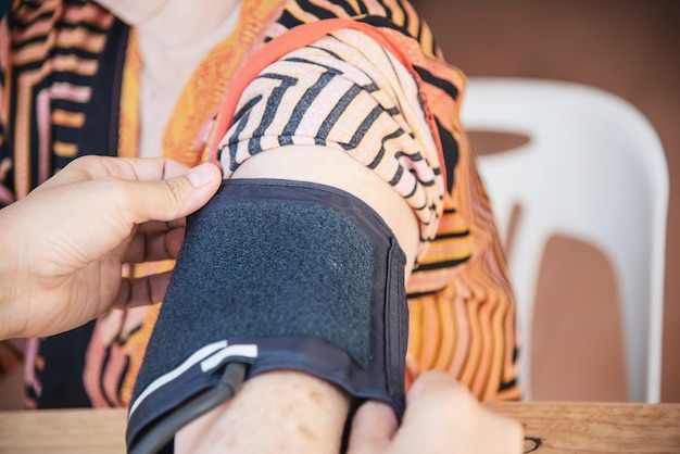 Velha senhora está sendo verificado a pressão arterial usando o conjunto de criança de monitor de pressão arterial