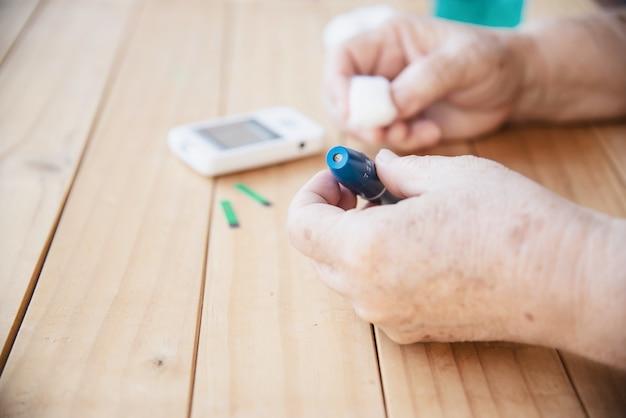 Velha senhora está testando o nível de açúcar no sangue usando o conjunto de criança de teste de açúcar no sangue