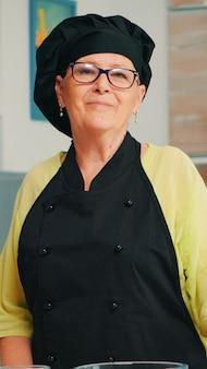 Velha senhora vestindo avental de chef e bonete na cozinha de casa com farinha na mesa para assar, olhando para a câmera e sorrir. padeiro idoso aposentado preparando ingredientes de padaria para cozinhar pães e bolos caseiros