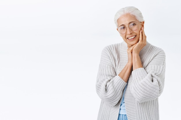 Velha sorridente e feliz idosa de óculos com cabelos grisalhos, olhando para a câmera encantada e alegre, sorrindo ao tocar o rosto e contemplar o neto brincando