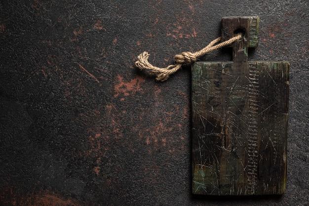 Velha tábua de madeira na mesa de pedra preta da cozinha