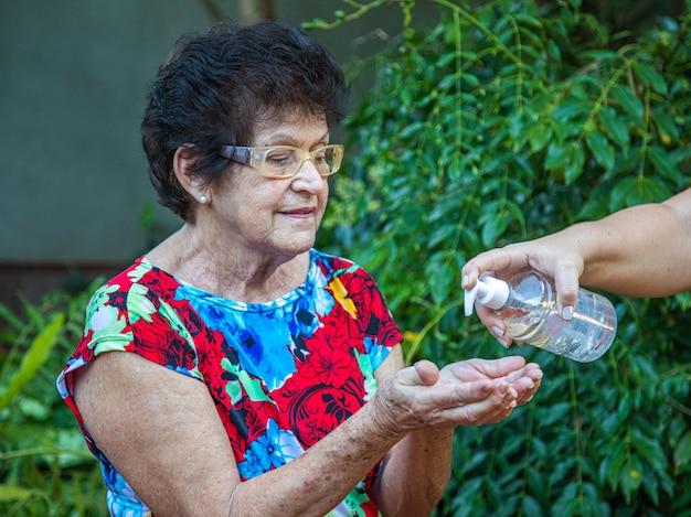 Velha usando desinfetante para as mãos