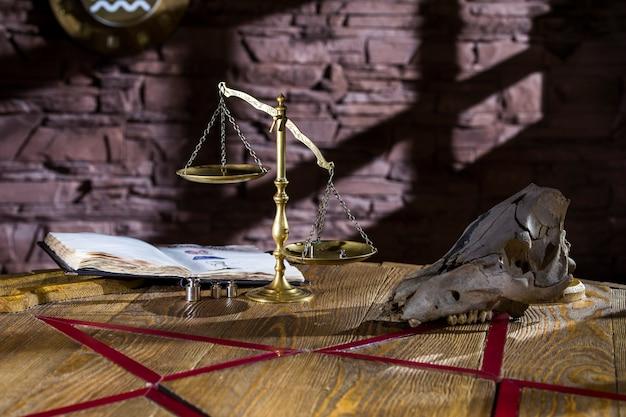 Velhas balanças em cima da mesa ficam perto do crânio e livros