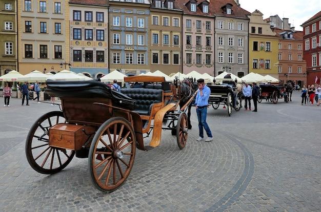 Velhas carruagens puxadas por cavalos aguardam os turistas na praça do mercado da cidade velha, no centro de varsóvia