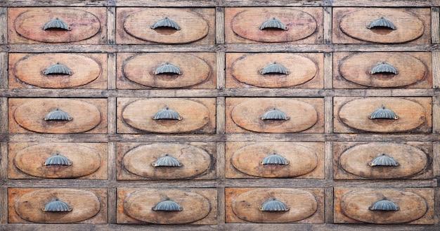Velhas gavetas de madeira com alças de metal na farmácia vintage.