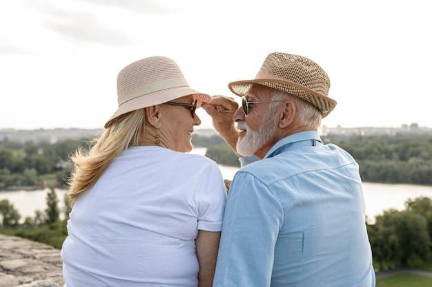 Velho, agarrando o chapéu de uma mulher