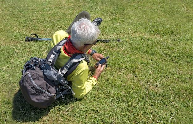 Velho alpinista deitado em um prado e olhando para o navegador portátil