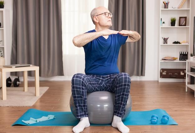 Velho ativo praticando esportes em seu apartamento aconchegante usando bola suíça e tapete de ioga