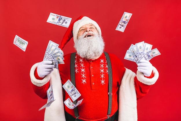 Velho barbudo fantasiado de papai noel segurando dinheiro em pé isolado sobre fundo vermelho