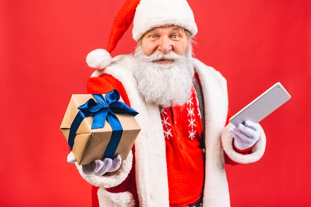 Velho barbudo fantasiado de papai noel segurando um tablet e um presente em pé isolado sobre fundo vermelho