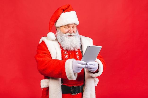 Velho barbudo fantasiado de papai noel segurando um tablet isolado sobre fundo vermelho