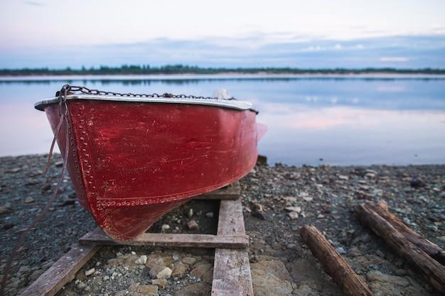 Velho barco a remos vermelho deitado na costa à noite.