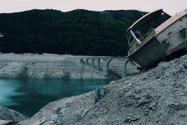 Velho barco cinza em uma superfície rochosa perto de uma ponte em arco no corpo de água, rodeado por árvores
