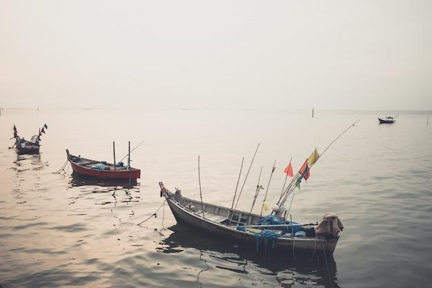 Velho barco de pesca ao pôr do sol na praia do mar