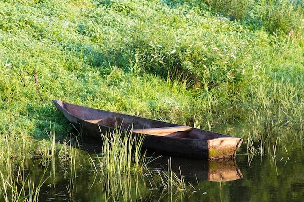 Velho barco de pesca de madeira ancorado na margem verde do rio