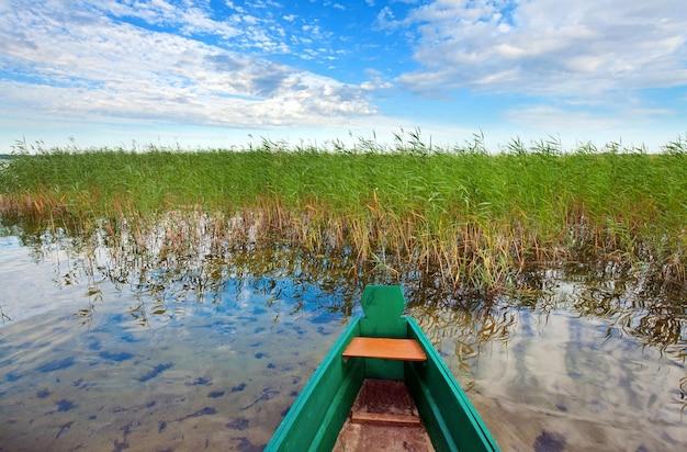 Velho barco de pesca de madeira na margem do lago de verão (svityaz, ucrânia)