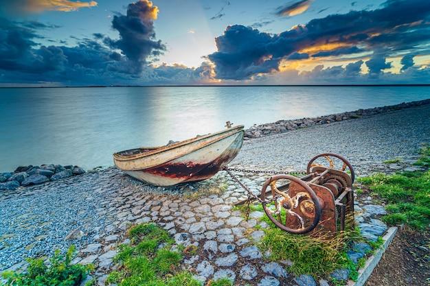 Velho barco de pesca enferrujado na encosta ao longo da margem do lago