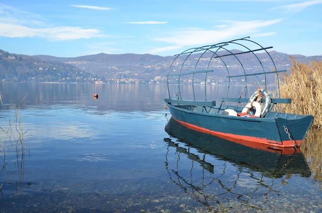 Velho barco de pesca no lago com montanhas